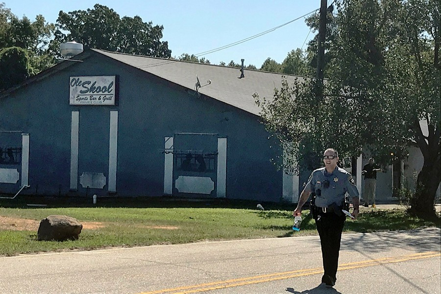 A Lancaster County Sheriff's deputy walks around the Old Skool Sports Bar and Grill, the scene of a shooting early in the morning, north of Lancaster, SC on September 21, 2019 — AP photo