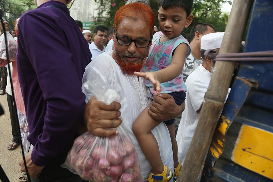 A man buying onion from a TCB sale point near the Jatiya Press Club in the city on Sunday. The Trading Corporation of Bangladesh (TCB) started selling onion under open market sale in the wake of sudden price hike of the essential kitchen item — FE photo