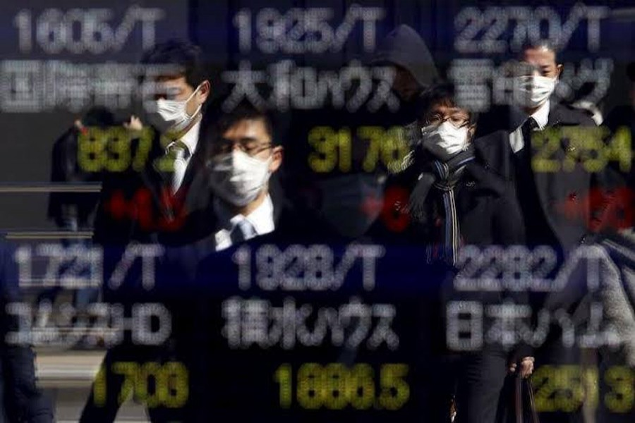 Pedestrians wearing masks are reflected in an electronic board showing various stock prices outside a brokerage in Tokyo, Japan, February 26, 2016. Reuters/Files