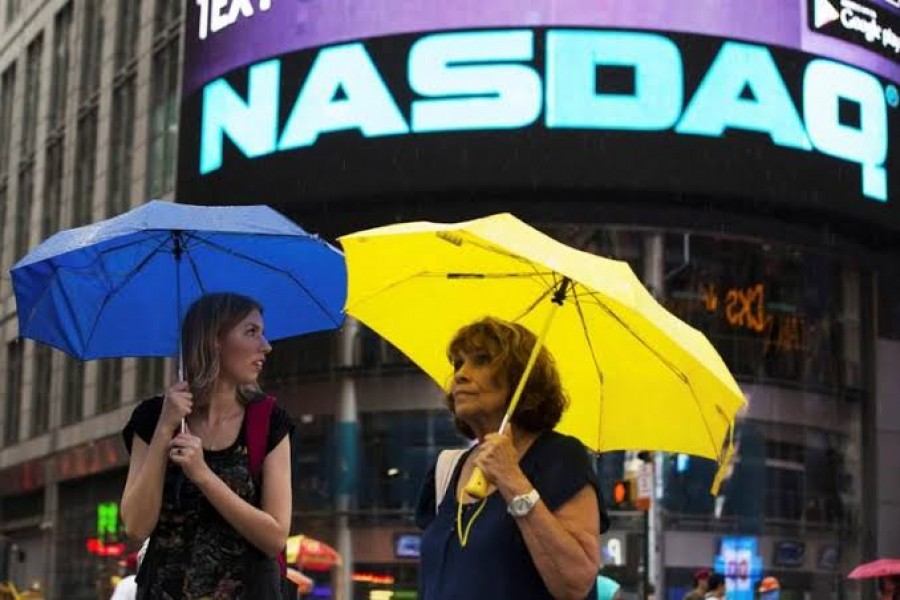 Two women hold umbrellas as they walk past the Nasdaq MarketSite in New York's Times Square, August 22, 2013. Reuters/Files