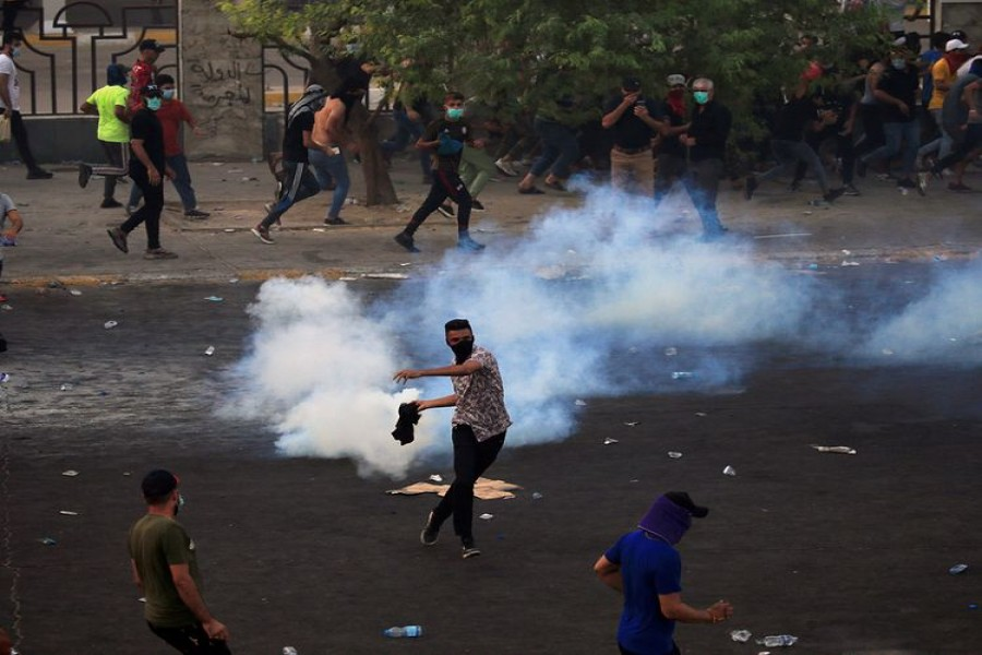 A demonstrator prepares to throw a tear gas canister used by Iraqi security forces as others disperse during a protest over unemployment, corruption and poor public services, in Baghdad, Iraq October 2, 2019 - Reuters