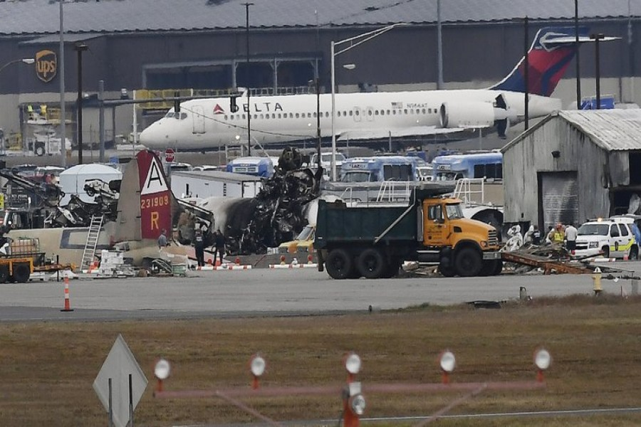 A Delta commercial airline plane taxis to take-off behind investigators at the wreckage of World War II-era bomber plane that crashed at Bradley International Airport in Windsor Locks, Conn., Wednesday, Oct. 2, 2019. (AP Photo/Jessica Hill)
