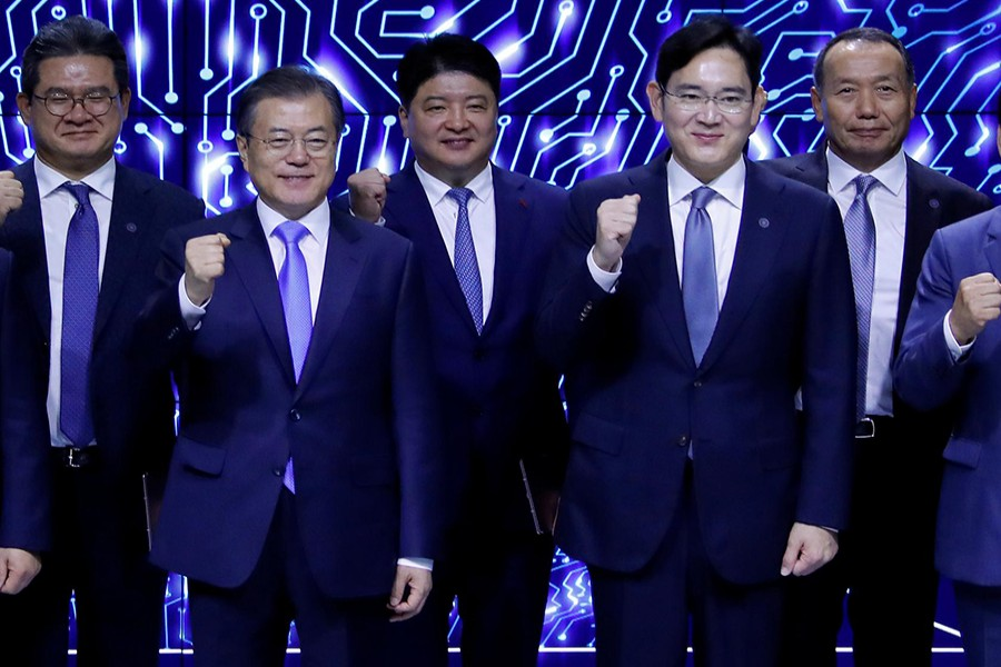 South Korean President Moon Jae-in and Samsung Electronics Vice Chairman, Jay Y Lee pose for a group photo after a signing ceremony at Samsung Display's factory in Asan, South Korea on October 10, 2019 — Yonhap via REUTERS