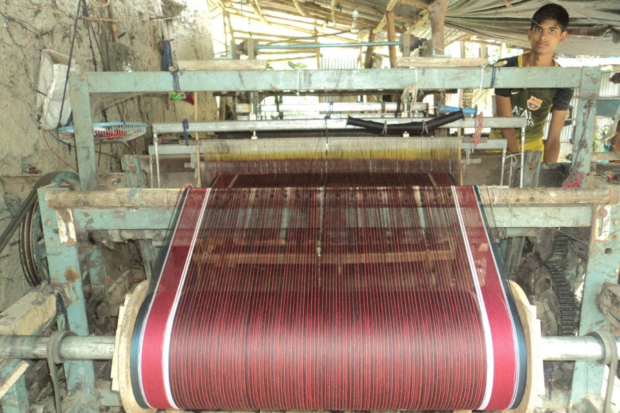 A young weaver weaving gamchha at a small factory in Adamdighi upazila of Bogura district       — FE Photo