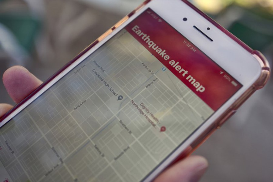 A mobile phone customer looks at an earthquake warning application on their phone in Los Angeles — AP file photo used for representational purpose