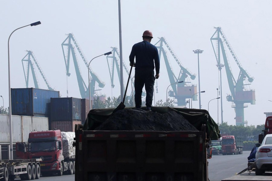 A labourer loading coal in a truck next to containers outside a logistics centre near Tianjin Port, in northern China	— Reuters