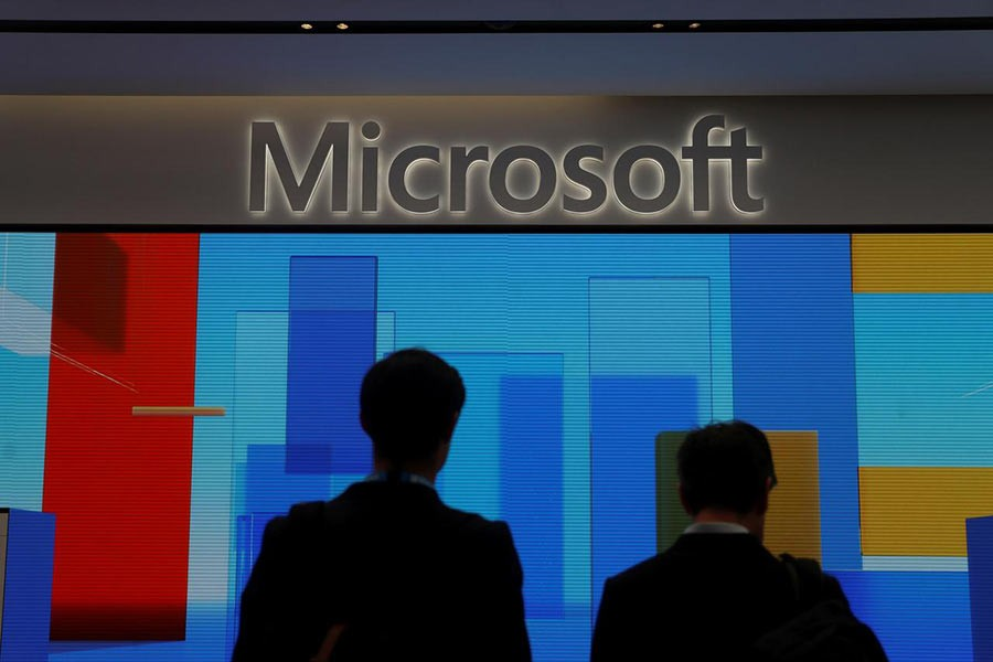 Visitors standing in front of a display screen at Microsoft's new Oxford Circus store ahead of its opening in London, Britain this year. -Reuters  File Photo