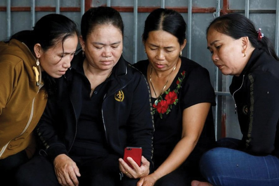Relatives of Anna Bui Thi Nhung, a Vietnamese suspected to be among dead victims found in a lorry in Britain, reading news about her at her home in Nghe An province, Vietnam, on October 26, 2019. 	—Photo: Reuters