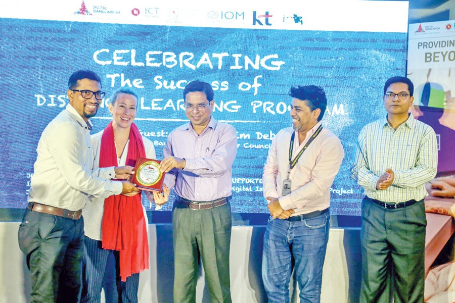 Parthapratim Deb, executive director, Bangladesh Computer Council (third from left) giving crest to Masum Al Reza, national programme coordinator, IOM Bangladesh (first from left) at the celebration event of completion of the Digital Island-Moheshkhali Project