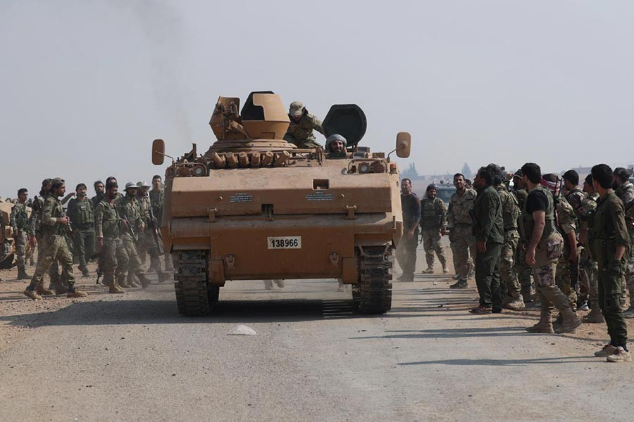 Turkey-backed Syrian rebel fighters gathering as a military vehicle advances near the border town of Tal Abyad in Syria on October 24, 2019. -Reuters Photo