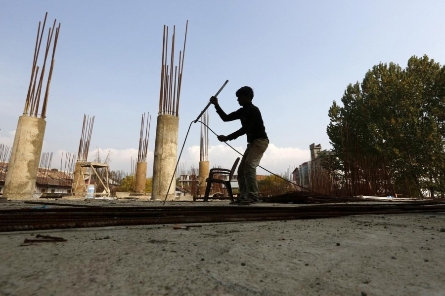 A migrant worker straightens an iron rod at the construction site of a parking lot in Srinagar October 30, 2019. Picture taken October 30, 2019. REUTERS/Danish Ismail