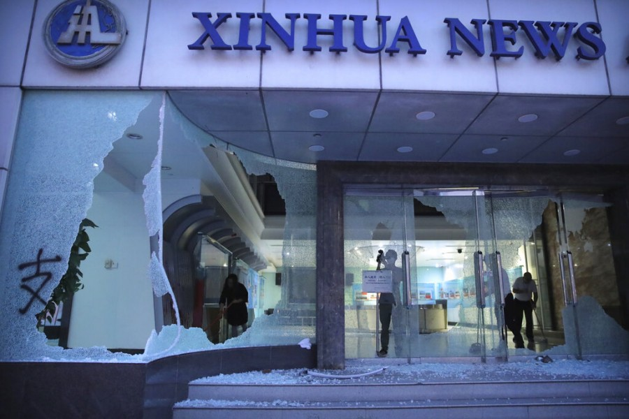 People stand inside the lobby of China's Xinhua News Agency after it was damaged by protesters in Hong Kong, Saturday, Nov 2, 2019. Photo: AP