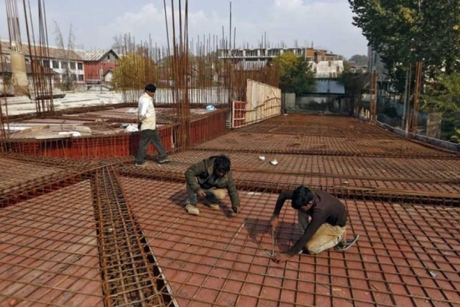 Migrant workers fasten iron rods together at the construction site of a parking lot in Srinagar Oct 30, 2019. REUTERS