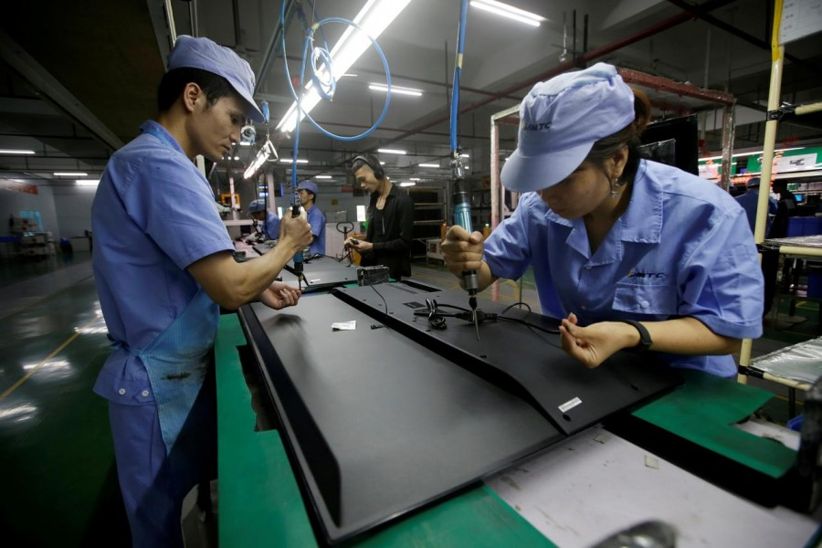 Employees work on the production line of a television factory under Zhaochi Group in Shenzhen, China August 8, 2019. Reuters/File Photo
