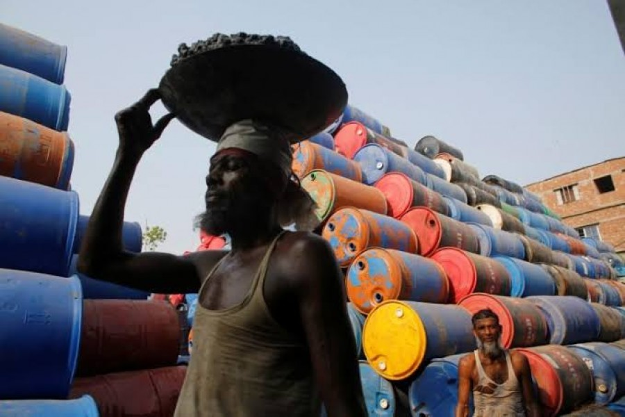 FILE PHOTO: Men work at a godown for storing empty oil drums by Buriganga river in Dhaka, Bangladesh May 18, 2014. REUTERS/Andrew Biraj/File Photo