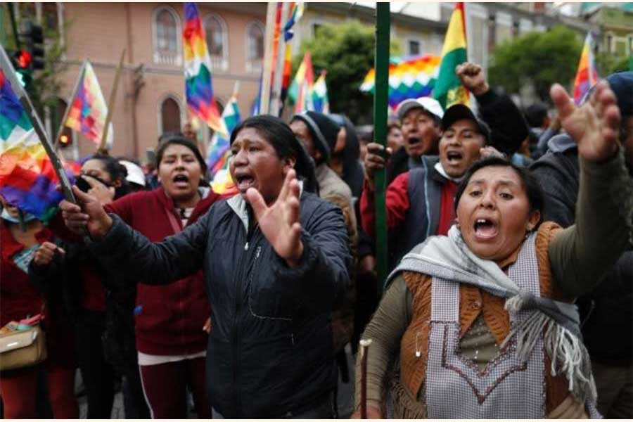 """Supporters of former president Evo Morales carry """"wiphala"""" flags that represent indigenous peoples. —Photo: AP"""