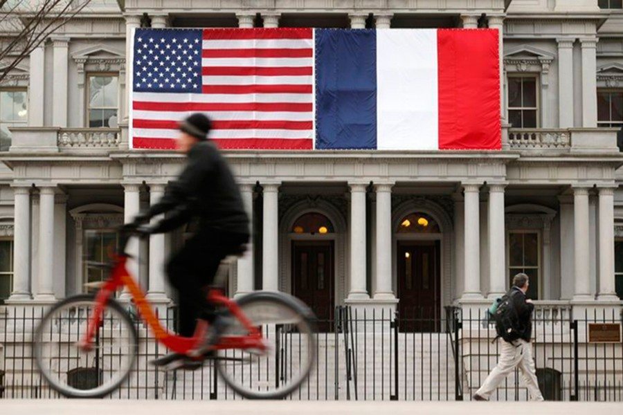 A cyclist passes the US and French flags flying over the Eisenhower Executive Office Building, which houses a majority of offices for White House staff, in Washington on February 10, 2014 — Reuters/Files