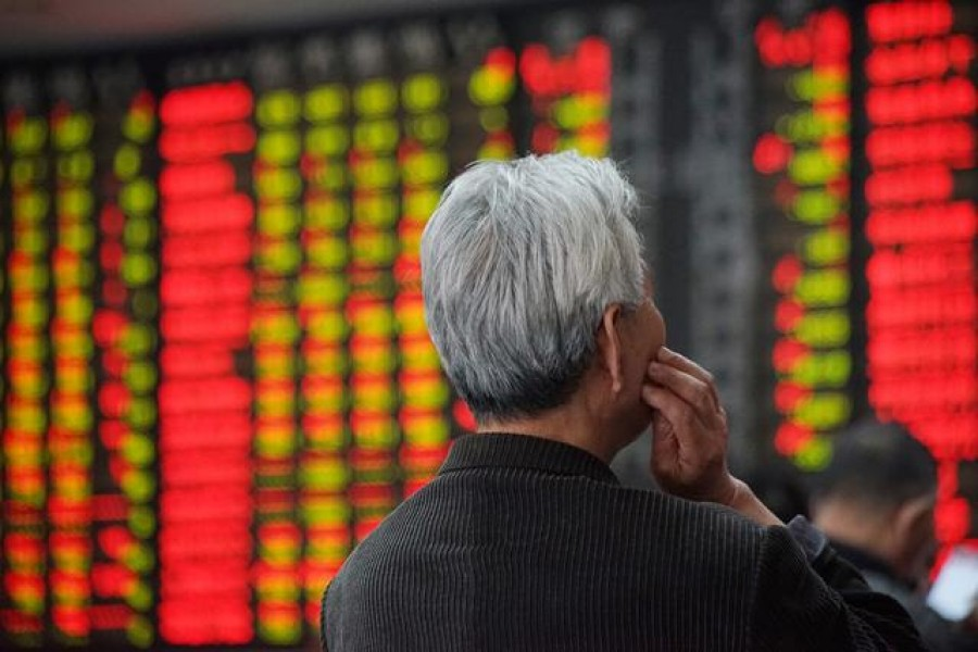 An investor looks at an electronic board showing stock information at a brokerage house in Nanjing, Jiangsu province, China, April 16, 2018. Reuters/Files