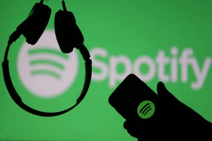 A smartphone and a headset are seen in front of a screen projection of Spotify logo, in this picture illustration taken April 1, 2018. REUTERS/Dado Ruvic/Illustration