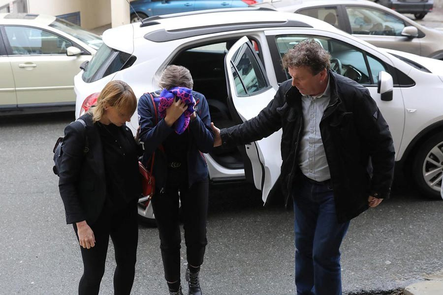 A British woman, accused of lying about being gang raped, covering her face as she arrives at the Famagusta courthouse in Paralimni, Cyprus on Monday. -Reuters Photo