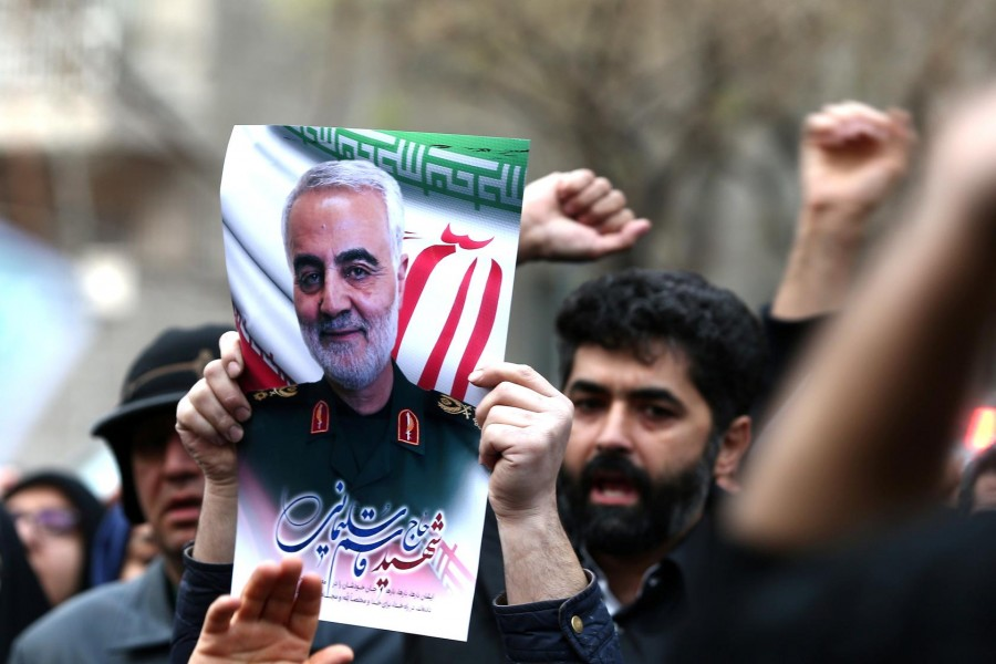 Iranian guards hold a picture of the late Iranian major-general Qassem Soleimani, during a protest against the killing of Soleimani, head of the elite Quds Force, and Iraqi militia commander Abu Mahdi al-Muhandis, who were killed in an air strike at Baghdad airport, in front of United Nation office in Tehran, Iran, January 03, 2020. WANA (West Asia News Agency)/Nazanin Tabatabaee via Reuters