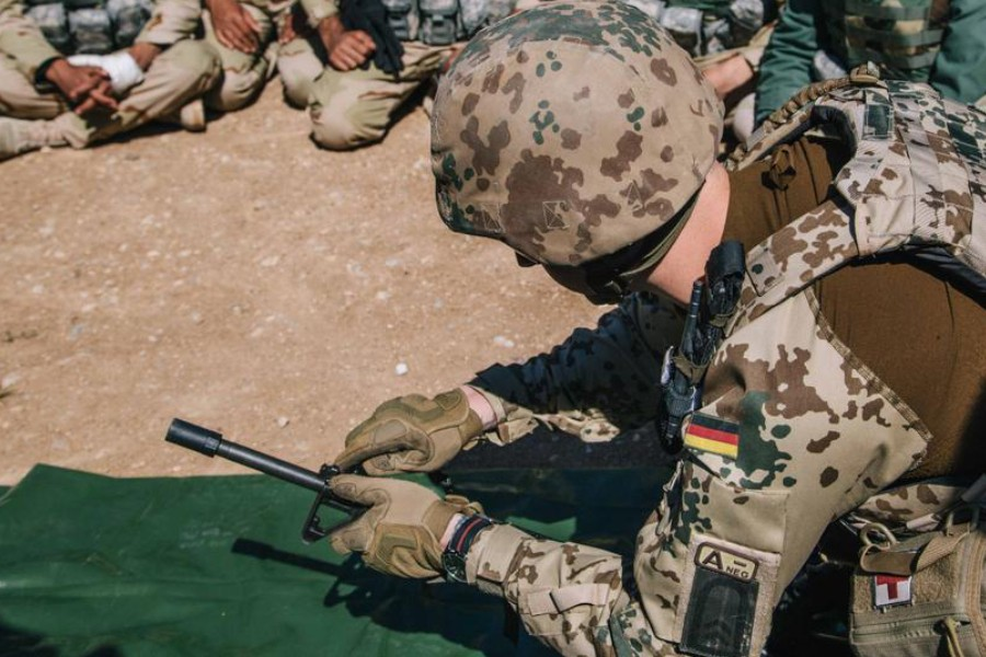 Kurdish Peshmerga soldiers watch a German army trainer assemble a rifle during a military training session, at Bnaslawa Military Base in Erbil, northern Iraq, March 9, 2016. (AP)