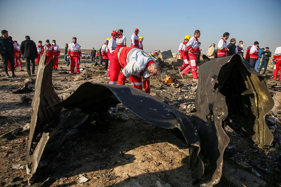 Red Crescent workers check the debris from the Ukraine International Airlines plane, that crashed after take-off from Iran's Imam Khomeini airport, on the outskirts of Tehran, Iran on January 8, 2020 — West Asia News Agency via Reuters
