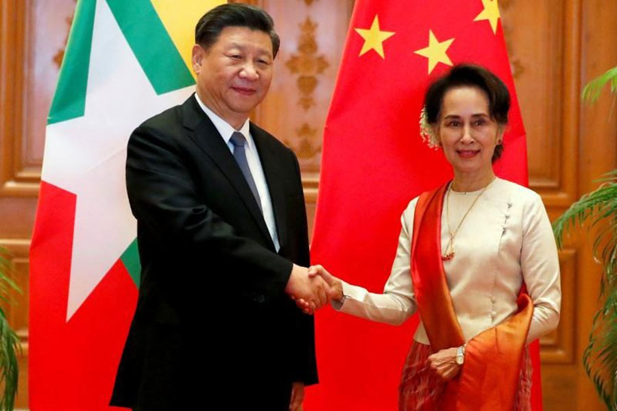 Myanmar State Counselor Aung San Suu Kyi shaking hands with Chinese President Xi Jinping at the Presidential Palace in Naypyitaw, Myanmar, on Saturday. -Reuters Photo