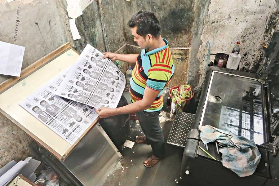 A pressman checking clarity of an election poster being printed at a press in Fakirerpool in the city on Monday ahead of the mayoral elections — FE photo