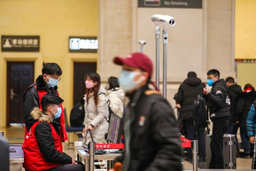 Staff members wearing masks monitor thermal scanners that detect temperatures of passengers at the security check inside the Hankou Railway Station in Wuhan, Hubei province, China on January 21, 2020 — China Daily via REUTERS