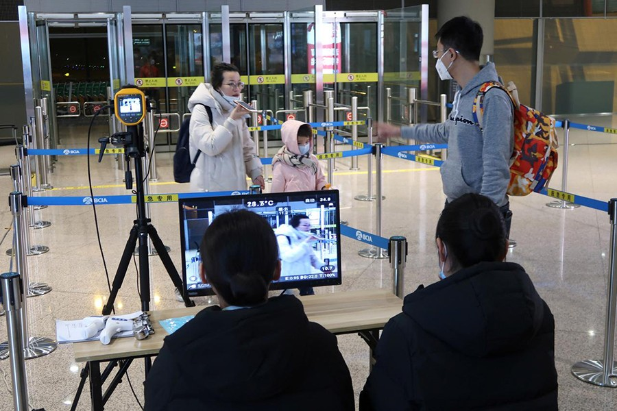 Staff members monitor thermal scanners that detect temperatures of passengers who have just landed at the arrival terminal in Beijing Capital International Airport in Beijing, China on January 25, 2020 — Reuters photo