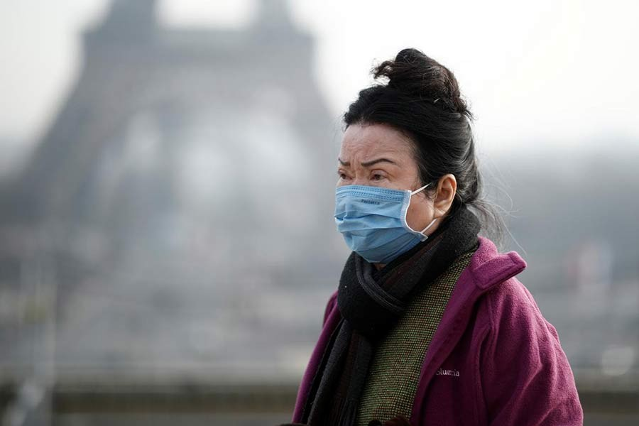 A woman wearing a face mask on the Trocadero esplanade in front of the Eiffel Tower in Paris, France, on Saturday, as France confirmed three cases of the new coronavirus. -Reuters Photo