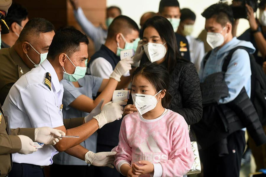 Health workers using infrared thermometers to check the temperature of tourists who arrive at Bangkok's Don Mueang Airport, Thailand, on Saturday. -Reuters Photo