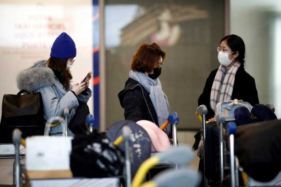 Tourists from an Air China flight from Beijing wear protective masks as they arrive at Charles de Gaulle airport in Paris, France, Jan 26, 2020. REUTERS