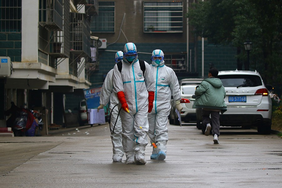 Workers from local disease control and prevention department in protective suits disinfect a residential area following the outbreak of a new coronavirus, in Ruichang, Jiangxi province, China on January 25, 2020 — cnsphoto via Reuters