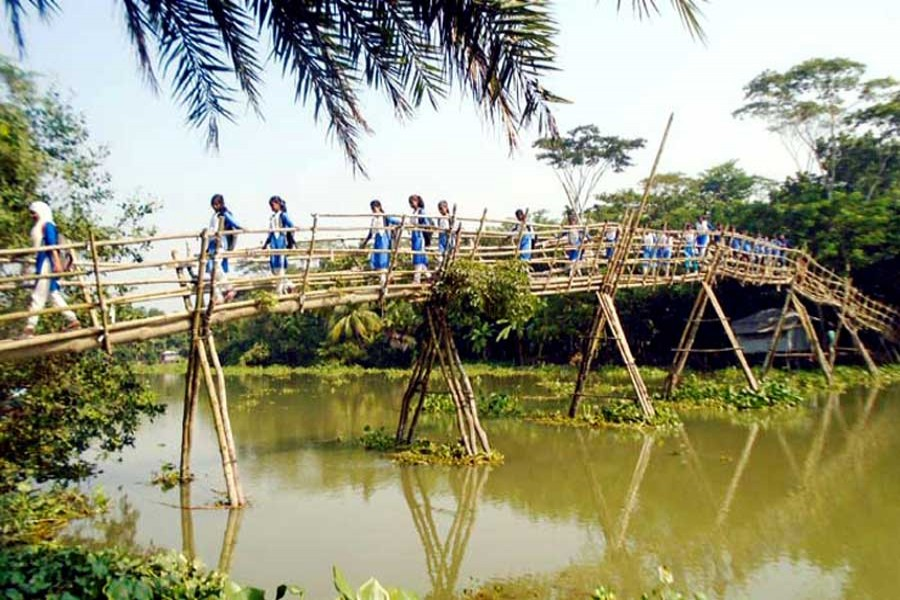 Some students crossing the Chitra river by using a bamboo bridge under Bagharpara upazila of Jashore district 	— FE Photo