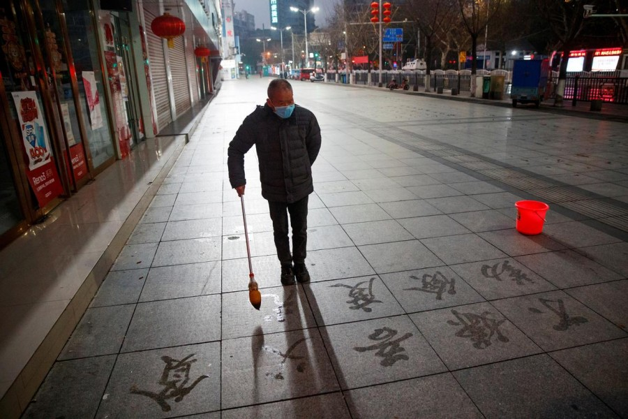 A man wears a face mask as he practices calligraphy of Chinese characters on a pavement as the country is hit by an outbreak of the novel coronavirus in Jiujiang, Jiangxi province, China, February 3, 2020. Reuters