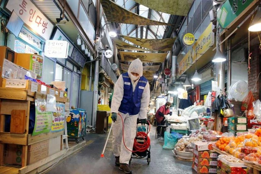 An employee from a disinfection service company sanitizes at a traditional market in Seoul, South Korea, February 7, 2020.  REUTERS/Heo Ran