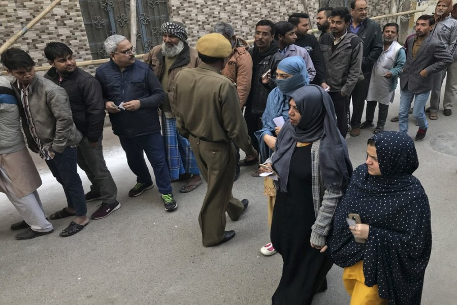 Muslim women arrive to cast their votes at Shaheen Public School, the polling booth closest to the Shaheen Bagh protest where Muslim women have been protesting for weeks against a new citizenship law, in New Delhi, India, Saturday, Feb. 8, 2020.   (AP Photo/Rishabh R. Jain)