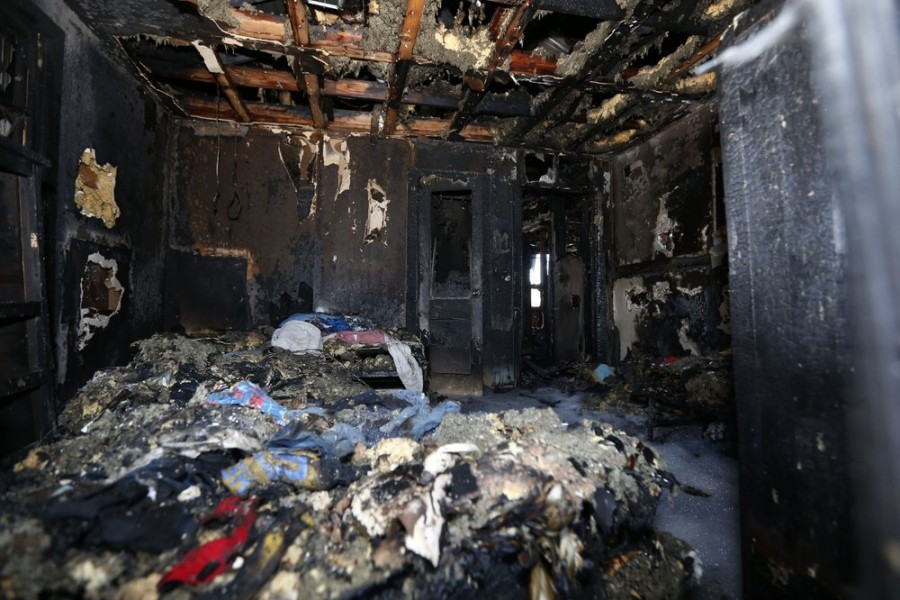 Burned clothes and the interior of a house are destroyed from a fatal fire on Saturday, Feb. 8, 2020 in Clinton, Mississippi, (AP Photo/Rogelio V. Solis)