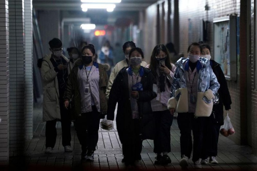 Workers wearing masks walk outside their dormitory, in an electronics manufacturing factory in Shanghai, China, as the country is hit by an outbreak of a new coronavirus, February 12, 2020. Reuters