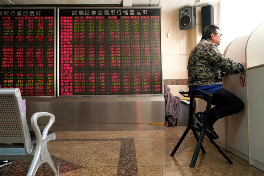 An investor sits next to a stock quotation board at a brokerage office in Beijing, China, January 3, 2020. Reuters