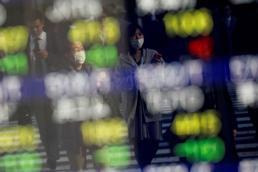 Pedestrians wearing facial masks are reflected on an electric board showing stock prices outside a brokerage at a business district in Tokyo, Japan January 30, 2020. Reuters/Files