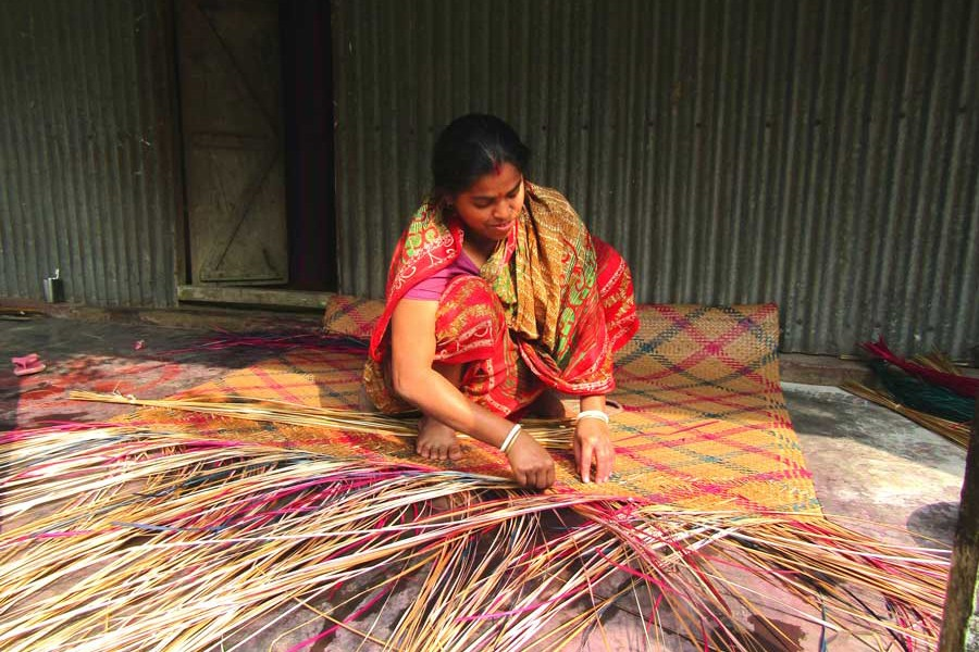 A female artisan weaving mat at her homestead in Mymensingh district    	— FE Photo
