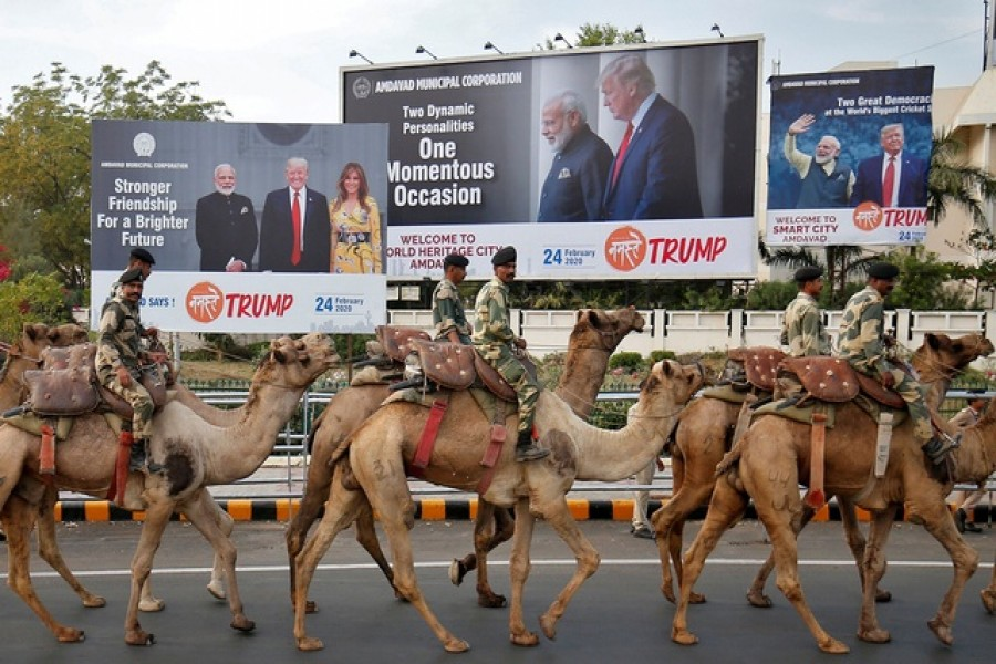 Border Security Force (BSF) soldiers ride their camels past hoardings with the images of India's prime minister Narendra Modi, US president Donald Trump and first lady Melania Trump, as they take part in a rehearsal for a road show ahead of Trump's visit, in Ahmedabad, India, February 21, 2020. Reuters