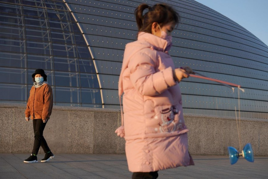 A girl wearing a face mask plays with a diabolo near the National Centre for the Performing Arts, following an outbreak of the novel coronavirus in the country, in Beijing, China, February 22, 2020. Reuters