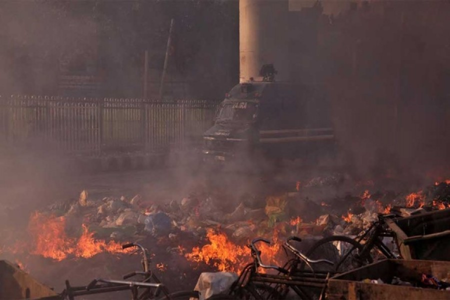 A police vehicle moves past burning debris that was set on fire by demonstrators in a riot affected area after fresh clashes erupted between people demonstrating for and against a new citizenship law in New Delhi, India, February 25, 2020 — Reuters