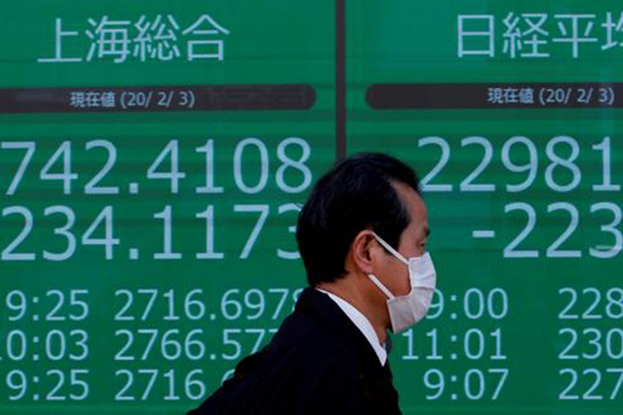 A man wearing a surgical mask stands in front of a screen showing Shanghai Composite index outside a brokerage in Tokyo, Japan, February 03, 2020 — Reuters
