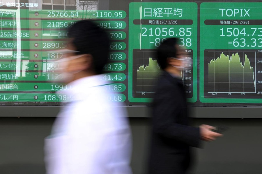 People wearing protective face masks, following an outbreak of the coronavirus, walk past a screen showing Nikkei index, outside a brokerage in Tokyo, Japan on February 28, 2020 — Reuters photo