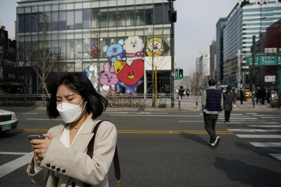A woman wearing a mask to prevent the coronavirus uses her mobile phone at a shopping district in Seoul, South Korea, February 24, 2020. REUTERS/Kim Hong-Ji